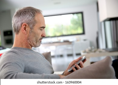 Senior man in couch reading message on smartphone