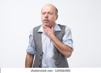 Senior man coughing being ill. Studio shoot. Flu or asthma health problem