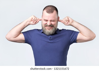 Senior man, covering closed ears, annoyed by loud noise or ignoring someone, not wanting to hear their side of story, isolated white background at studio . Negative facial emotion