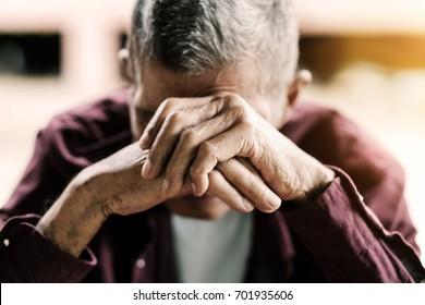 Senior Mann, der sein Gesicht mit seinen Händen bedeckt.Vintage-Ton