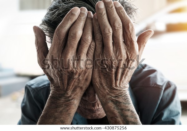 senior man covering his face with his hands.vintage tone