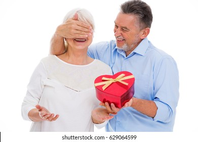 Senior man covering woman's eyes and holding heart-shaped box