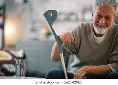 Senior man with crutch sitting on a sofa at home.