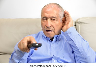 Senior man cupping his hand behind his ear to hear better to the television
