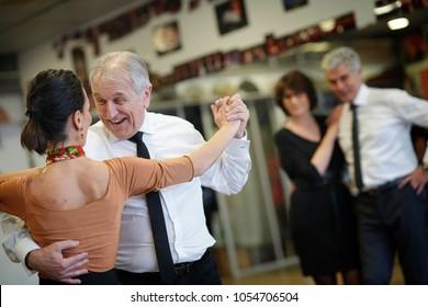 Senior man dancing with dance teacher during group class