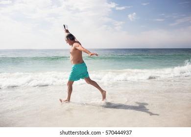 Senior man dancing on beach on a sunny day