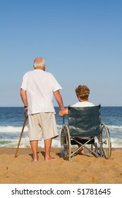 senior man and disable wife on beach