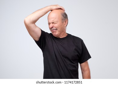 Senior man with disgust on his face sniffing something stinking, very bad smell isolated on gray background. Problem with sweat. Negative emotion facial expression