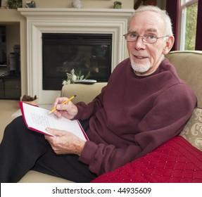 Senior man doing crossword on sofa