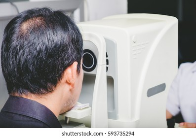 A senior man doing eyesight measurement with optical phoropter instruments at optician or ophthalmologist.