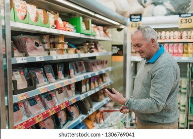 Senior man is doing his food shopping in the supermarket and is looking at his shopping list on his smart phone.