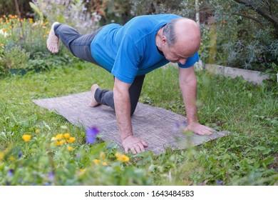 Senior man doing yoga in his garden Vyaghrasana or Tiger Pose.