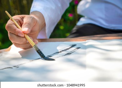 Senior man drawing bamboo tree by Asia; China brush with Asian stroke style. He's sitting in the relaxing bambook garden.