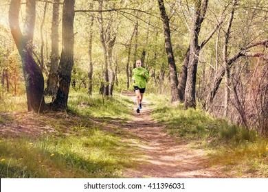 A senior man dressed in black and green is running in the forest, during a warm spring day
