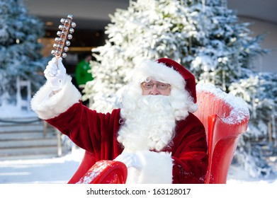A senior man dressed in a Santa Claus costume plays bells on the opening day of the Ideal Home Show Christmas 2013 at Earls Court in London on November 13, 2013.
