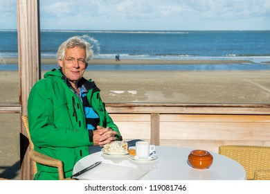 Senior man is drinking coffee with apple pie at the beach in winter