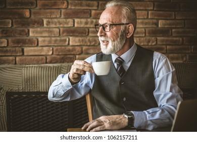 Senior man drinking coffee. Close up.