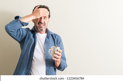 Senior man drinking coffee in a mug stressed with hand on head, shocked with shame and surprise face, angry and frustrated. Fear and upset for mistake.