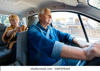 Senior man driving car while passenger sitting in back seat. Elderly woman is guiding driver during journey. They are in taxi.