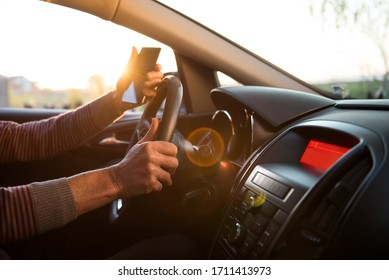 Senior man driving his car at sunset and holding smart phone in his hand.