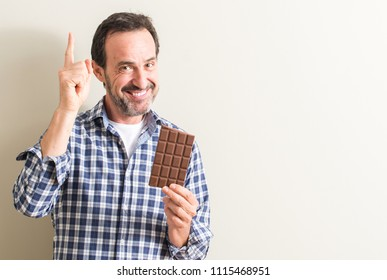 Senior man eating chocolate bar surprised with an idea or question pointing finger with happy face, number one