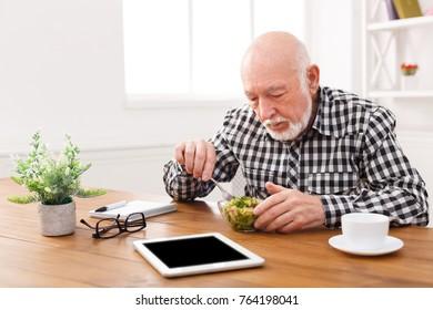 Senior man eating fresh salad. Mature male having healthy snack, healthcare, diet concept