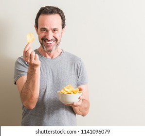 Senior man eating potato chips with a happy face standing and smiling with a confident smile showing teeth