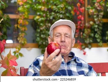 Senior man eating red organic apple in courtyard