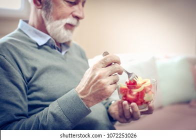 Senior man eating vegetable. Close up. Focus is on hands.