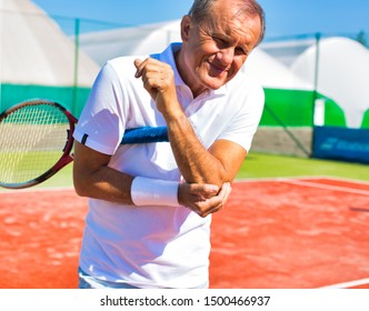 Senior man with elbow pain standing during tennis match on sunny day
