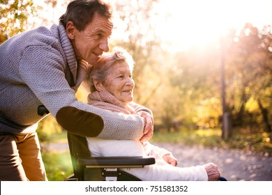 Senior man and elderly woman in wheelchair in autumn nature. Man with his mother on a walk.