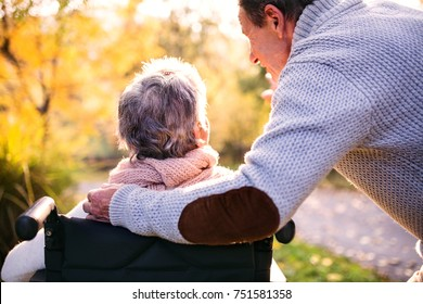 Senior man and elderly woman in wheelchair in autumn nature. Man with his mother or a wife on a walk. Rear view.