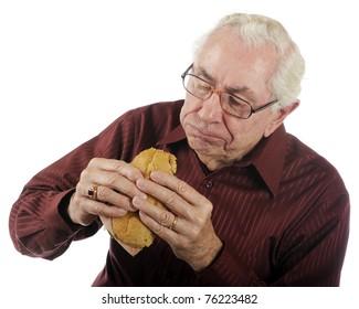 A senior man enjoying a big bite off his submarine sandwich.