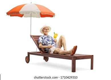 Senior man enjoying a cocktail drink on a sunbed under an umbrella isolated on white background