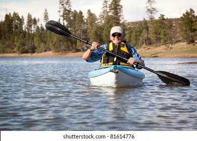 Senior Man Enjoying Kayaking on Lake