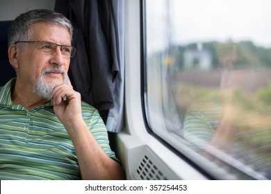 Senior man enjoying a train travel - leaving his car at home, he savours the time spent travelling, looks out of the window, has time to admire the landscape passing by
