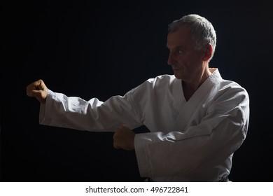 Senior man enjoys practicing karate indoor.Senior man practicing karate