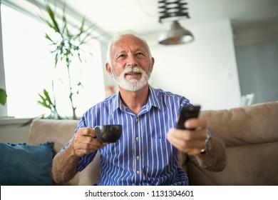 Senior man enjoys watching tv at home. Senior man watching tv and drink coffee