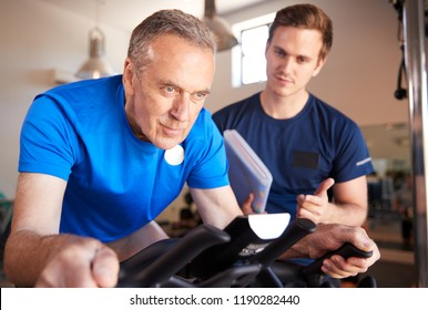 Senior Man Exercising On Cycling Machine Being Encouraged By Personal Trainer In Gym