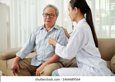 Senior man in eyeglasses sitting on sofa and breathing while young female nurse in white coat listening to his heartbeat with stethoscope at hospital