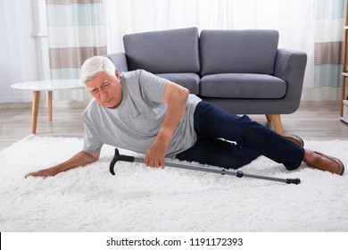 Senior Man Fallen On Carpet With Walking Stick
