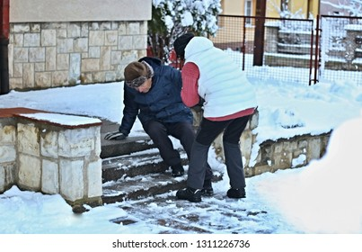 Senior man falling down from the slippery, icy and snowy stairs in front of a house. His wife trying to help him. Prevention of safety to injure old people before slipping accident on the stairs.