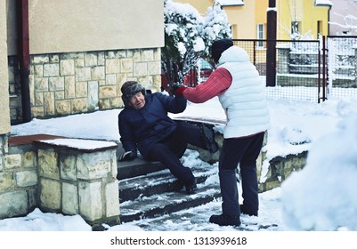 Senior man falling down from the slippery, icy and snowy stairs in front of a house. His wife is trying to help him. Prevention of safety to injure old people before slipping accident on the stairs.