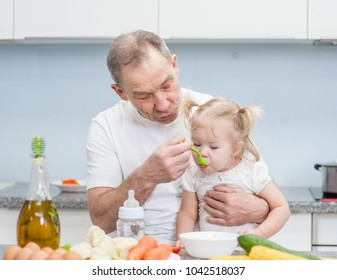 Senior man feeding baby girl with a spoon at kitchen