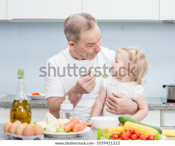 Senior man feeding baby girl with a spoon at kitchen