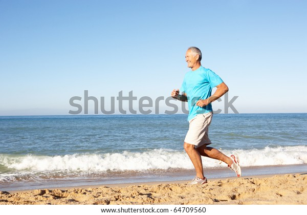 Senior Man In Fitness Clothing Running Along Beach