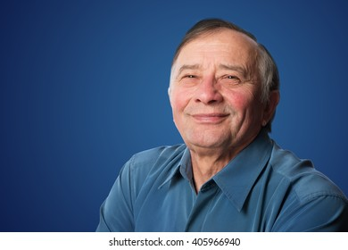 Senior man with a friendly smile standing against a blue background