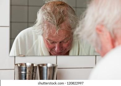 Senior man in front of mirror in bathroom.