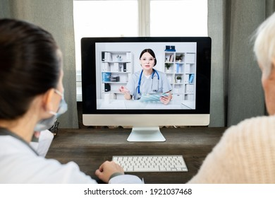 Senior man and general practitioner sitting by table in front of computer monitor with young female doctor on screen during consultation