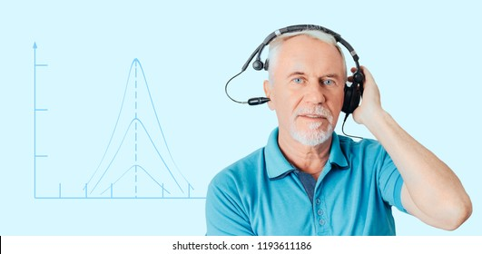 Senior man getting a hearing test , tympanogram on the background. impedance audiometry, measurement of the pressure in the middle ear.
